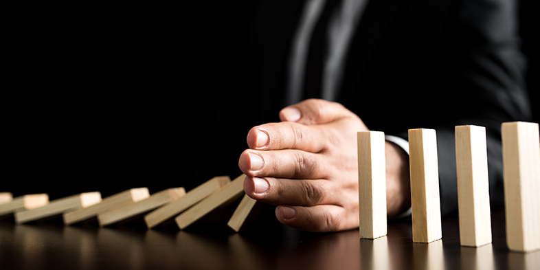 Businessman preventing Dominoes Chain from toppling