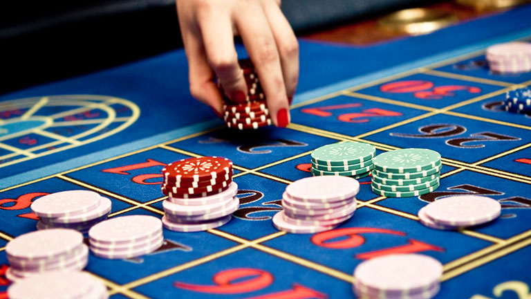Blue casino roulette table and female hand holding gambling chips