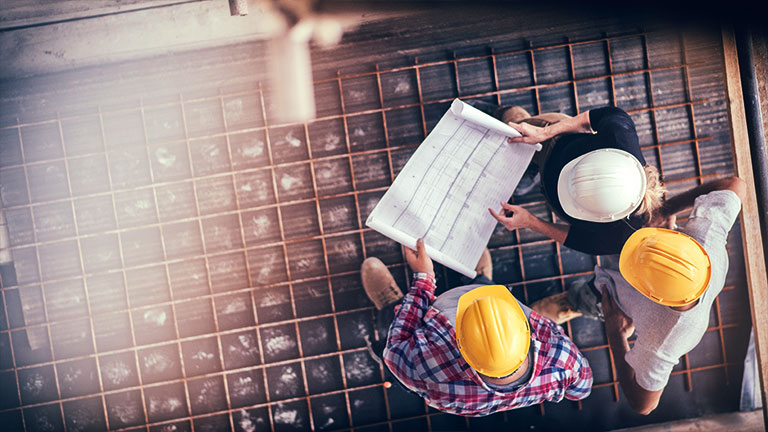 High angle view of three people with helmets, female architect, foreman and engineer on a construction site, looking down on a blueprint, copy space